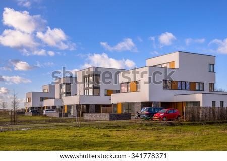Modern geometric family houses along a green modern residential suburban street, Groningen, Netherlands - stock photo
