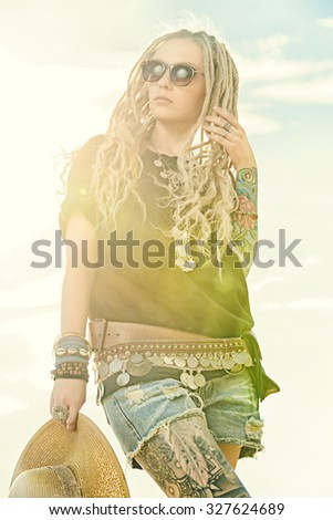 Modern girl with long blonde dreadlocks standing outdoor over blue sky. Boho style fashion.  - stock photo