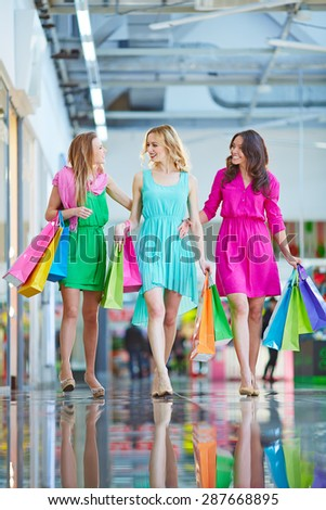 Modern girls with paperbags shopping in the mall - stock photo
