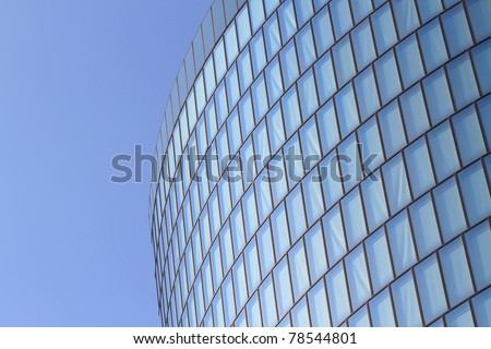 Modern glas facade of office tower in front of blue sky - stock photo