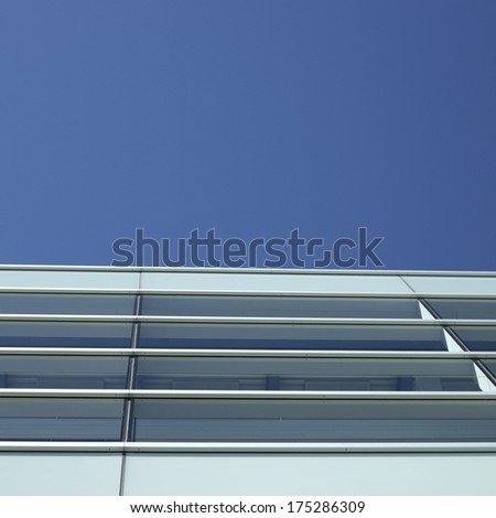 Modern glass and metal building with blue sky - stock photo