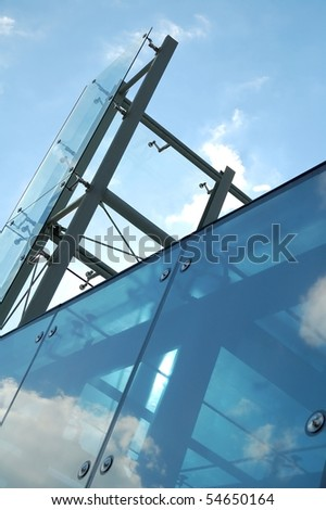 Modern glass and steel construction with blue sky - stock photo