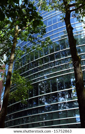 modern glass building reflecting several trees and a blue sky - stock photo