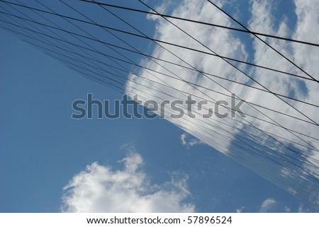Modern glass building reflecting sky and clouds. - stock photo