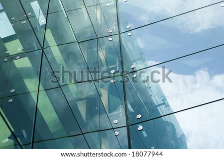 Modern glass building - sky and clouds reflection - stock photo