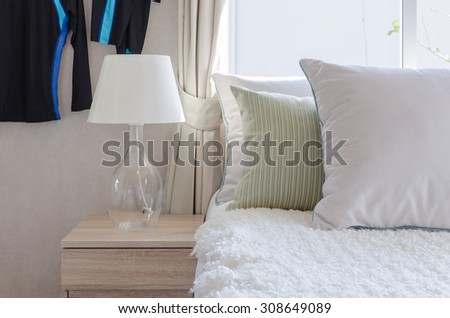 modern glass lamp on wooden side table in bedroom at home - stock photo