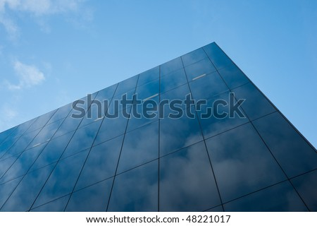 Modern glass office block window against sky with reflection