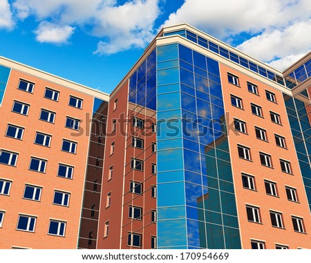 Modern glass reflective city business office buildings over blue sky with clouds - stock photo