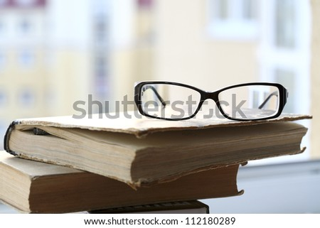 modern glasses and old book