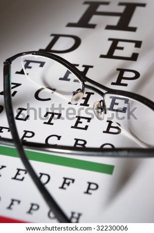 Modern glasses and snellen eye test chart differential focus - stock photo