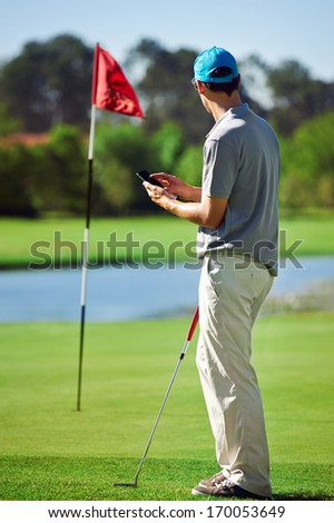 modern golf man with smart phone taking score on mobile gps device next to green - stock photo