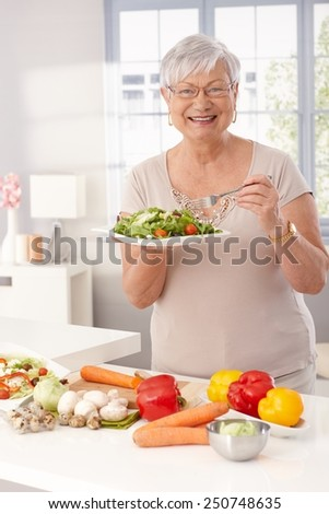 Modern grandmother eating fresh green salad and vegetables in kitchen, smiling happy, looking at camera. - stock photo