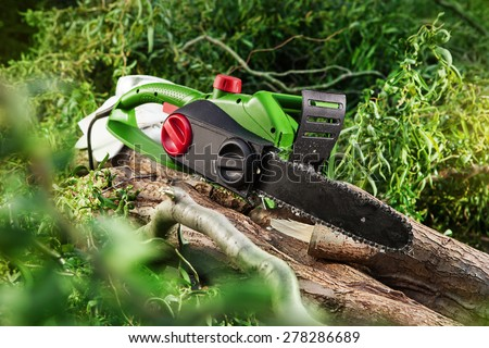modern green electrical chainsaw in forest - stock photo