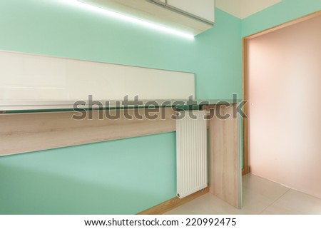 Modern green kitchen with wooden worktop and glass door - stock photo