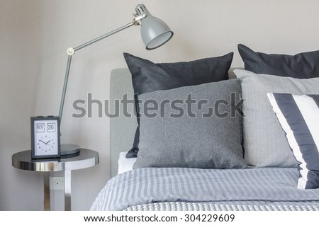 modern grey lamp with alarm clock on side table in bedroom at home - stock photo