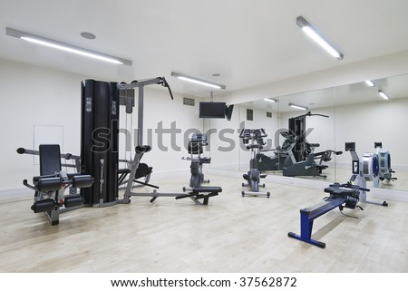 modern gym in leisure center with mirror wall and fitness machines - stock photo