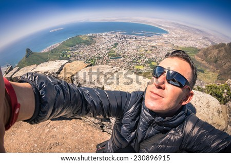 Modern handsome young man taking a selfie at Table Mountain in Cape Town - Adventure travel lifestyle enjoying connection with nature - Trip excursion in South Africa at nature wonder destination  - stock photo