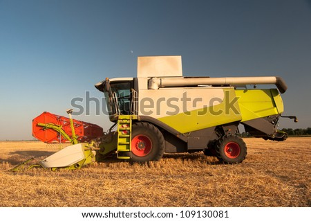Modern harvester combine standing on the field on sunny summer day. - stock photo