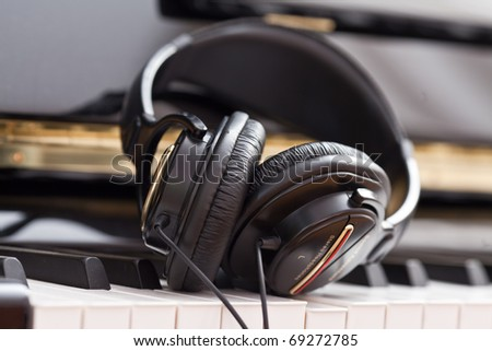 Modern headphones on keyboard of classic black grand piano - stock photo