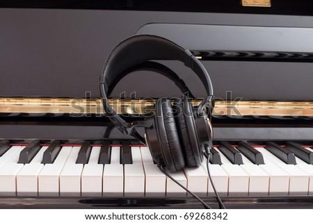 Modern headset on a classic black grand piano keyboard. - stock photo