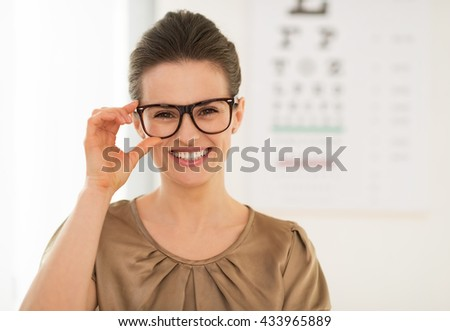 Modern health care. Happy young woman wearing eyeglasses in front of Snellen chart - stock photo