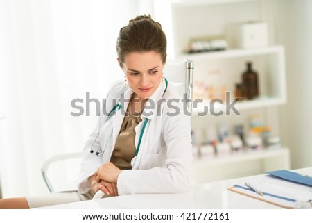 Modern health care. Pensive female doctor sitting at a desk in the office - stock photo
