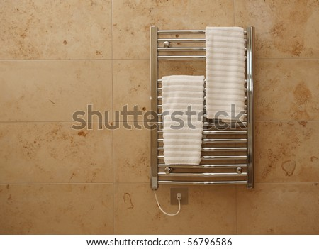 Modern heated towel rail on tiled bathroom wall. - stock photo