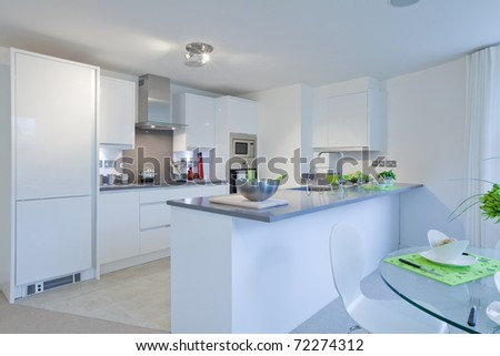 Modern high gloss finish kitchen incorporating built-in appliances, granite worktops and breakfast area with dressed table - stock photo
