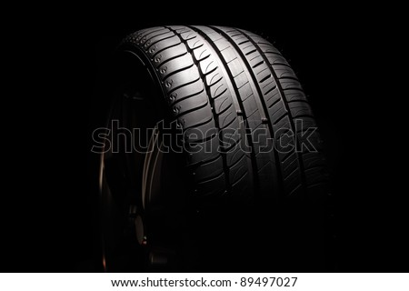 Modern high-performance sport summer tyre isolated on a black background. Horizontal composition. - stock photo