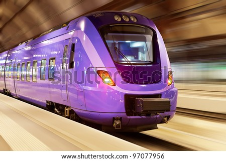 Modern high speed train with motion blur effect at the railway station - stock photo