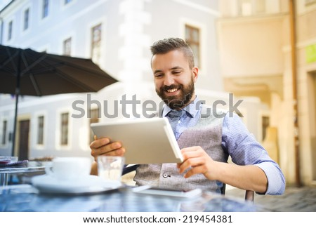 Modern hipster businessman drinking espresso coffee in the city cafe during lunch time and working on tablet - stock photo