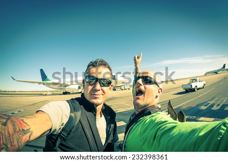 Modern hipster young friends taking a selfie at international airport - Adventure travel lifestyle enjoying moment and sharing happiness - Trip together around the world as alternative lifestyle - stock photo
