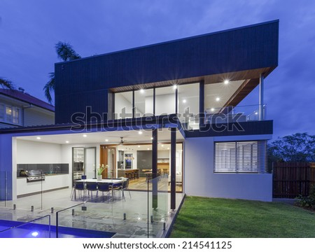 Modern home at dusk with pool and bbq area - stock photo