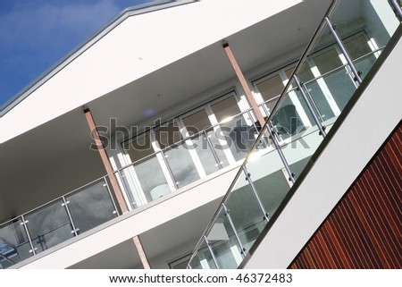 Modern Home exterior with glass, timber and steel construction.  Features balcony, railings and chairs.  Angled perspective and blue sky.