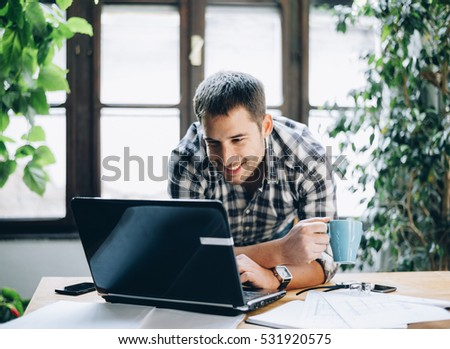 Modern home office concept for freelance professions. Cool workspace green and light interior. Happy young man working on his project on laptop.