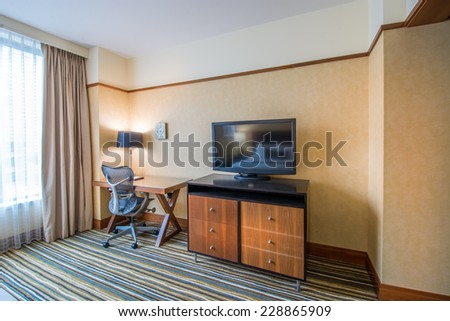 Modern home office space with desk, chair, TV and dresser. Interior design. - stock photo