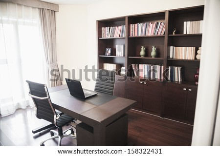 Modern home office with bookshelves - stock photo
