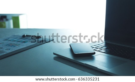 Modern home office with computer and laptop, folder, phone lying on the desk