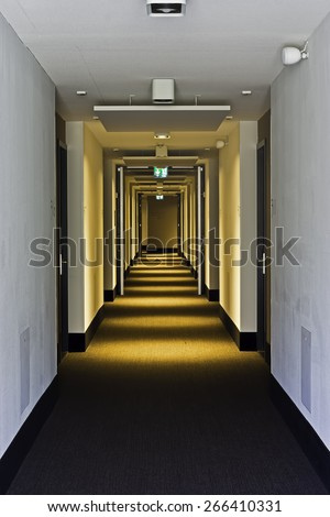 Modern hotel corridor with brown carpet  Walls and ceiling white. Room numbers are painted on the wall next to the door. The lights in the ceiling are equipped with motion detectors for saving energy. - stock photo
