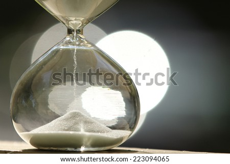 Modern Hourglass -- sand trickling through the bulbs of a crystal sand glass. every second counts. symbol of time. countdown. Sand clock. - stock photo