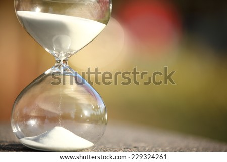 Modern Hourglass -- sand trickling through the bulbs of a crystal sand glass. every second counts. symbol of time. Christmas countdown. - stock photo