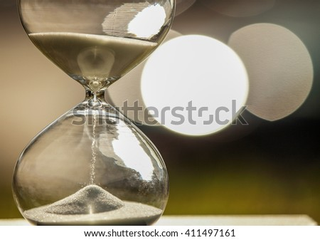 Modern Hourglass -- sand trickling through the bulbs of a crystal sand glass on bokeh background. every second counts. symbol of time. countdown. sandglass. - stock photo