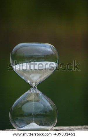 Modern Hourglass -- sand trickling through the bulbs of a crystal sand glass on dark background. - stock photo
