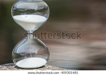 Modern Hourglass -- sand trickling through the bulbs of a crystal sand glass on dark background.