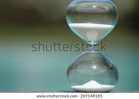 Modern hourglass with blur background -- sand trickling through the bulbs of a crystal sand glass. every second counts. symbol of time. summer countdown. - stock photo