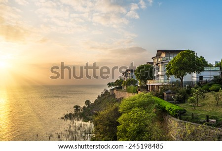 modern house aside the lake in sunset. - stock photo
