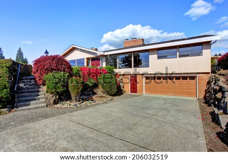 Modern house exterior with curb appeal. View of garage and driveway - stock photo