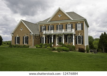 Modern House with landscaped lawn and garden on a bright but cloudy day - stock photo