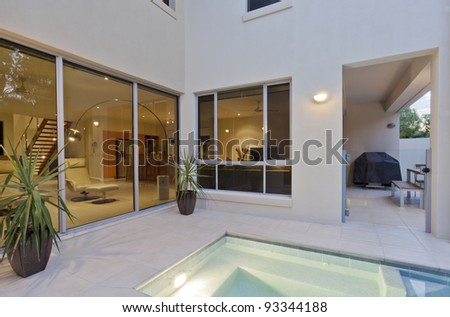 Modern house with living room overlooking the pool and backyard - stock photo