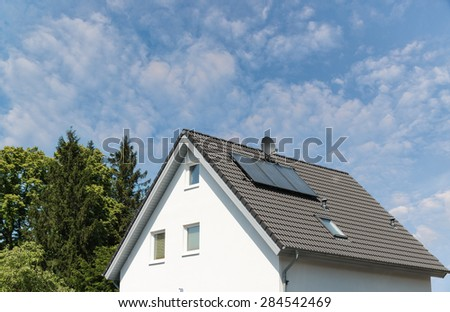 Modern house with solar panels and trees - stock photo